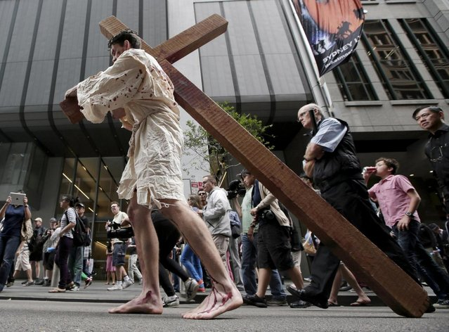 "David Carnell plays a part of Jesus Christ during a ""Journey to the Cross"" procession while celebrating Good Friday in Sydney, Australia, Friday, March 29, 2013. The annual event by Wesley Mission tells the Easter story in a modern Australia. (Photo by Rick Rycroft/AP Photo)"
