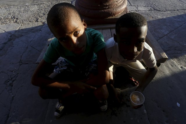 Children sit on the sidewalk during sunset in Havana October 26, 2015. (Photo by Reuters/Stringer)