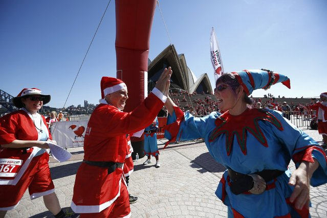 A Santa 'elf' congratulates a runner across the finish line after completing the annual Santa fun run from Darling Harbour to the Sydney Opera House, December 7, 2014. (Photo by Jason Reed/Reuters)