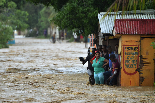 People try to cross the overflowing Rouyonne river in the commune of Leogane, south of Port-au-Prince, October 5, 2016. Haiti and the eastern tip of Cuba – blasted by Matthew on October 4, 2016 – began the messy and probably grim task of assessing the storm's toll. Matthew hit them as a Category Four hurricane but has since been downgraded to three, on a scale of five, by the US National Hurricane Center. (Photo by Hector Retamal/AFP Photo)