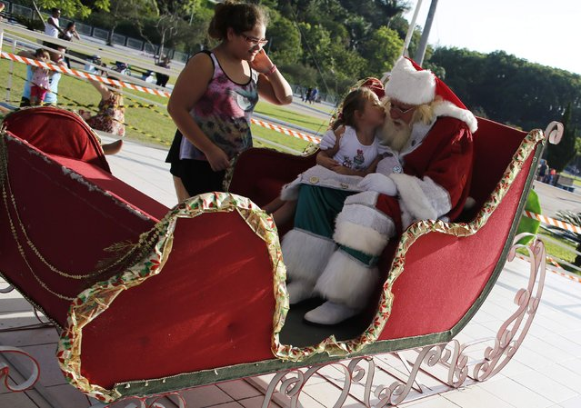 Vitor Martins, dressed as Santa, sits with a girl on his sledge in Sao Caetano do Sul's town square, near Sao Paulo, December 7, 2014. (Photo by Nacho Doce/Reuters)
