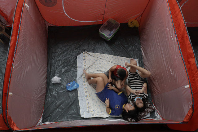 Residents stay inside an evacuation center as rains from a typhoon locally known as Gonistart start to pour in Manila, Philippines on Sunday, November 1, 2020. (Photo by Aaron Favila/AP Photo)