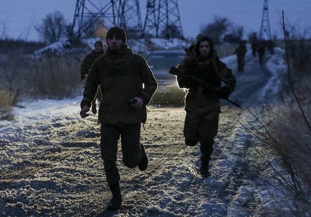 """Pro-Russian separatists from the Chechen """"Death"""" battalion run during a training exercise in the territory controlled by the self-proclaimed Donetsk People's Republic, eastern Ukraine, December 8, 2014. (Photo by Maxim Shemetov/Reuters)"""