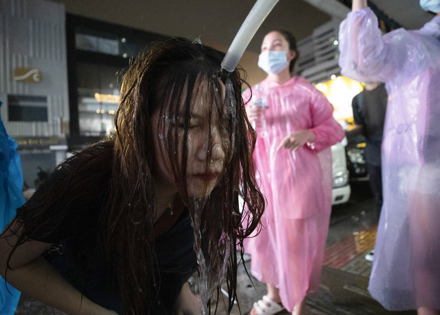 In this October 16, 2020, file photo, a demonstrator washes her face after police water cannons dispersed them from a protest venue in Bangkok, Thailand. Fed up with an archaic educational system and enraged by the military's efforts to keep control over their nation, a student-led campaign has shaken Thailand's ruling establishment with the most significant campaign for political change in years. (Photo by Sakchai Lalit/AP Photo/File)