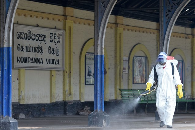 A health worker sprays disinfectant at Slave Island railway station as a preventive measure against the Covid-19 coronavirus in Colombo on October 30, 2020 after a three-day curfew was announced to contain the spread of the coronavirus. (Photo by Lakruwan Wanniarachchi/AFP Photo)