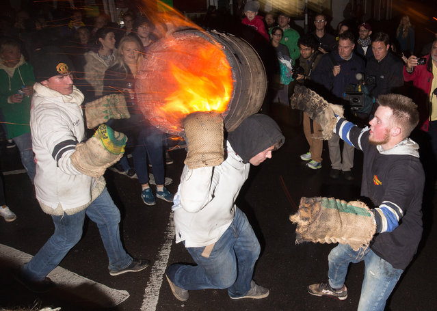 A boy runs with a burning barrel soaked in tar at the annual Ottery St Mary tar barrel festival on November 5, 2015 in Ottery St. Mary, England. The tradition, which is over 400 years old, sees competitors (who must have been born in the town to take part) running with burning barrels on their backs through the village, until the heat becomes too unbearable or the barrel breaks down, starting with junior barrels carried by children and continuing all evening with ever larger and larger barrels. (Photo by Matt Cardy/Getty Images)