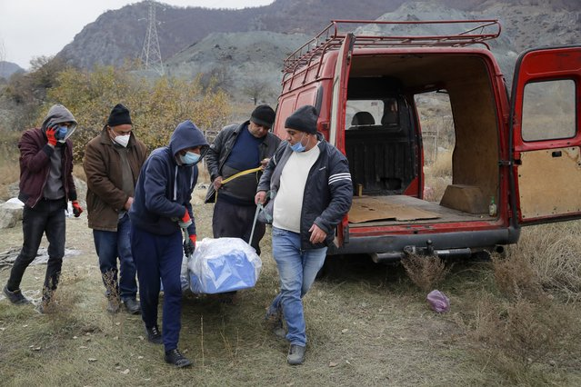 Ethnic Armenians carry a coffin with the body of their relative Sergei Gabrilyan, moved from a grave, to repatriate his remains to Armenia, in Kalbajar in separatist region of Nagorno-Karabakh, Monday, November 16, 2020. It is unclear when any civilians might try to settle in Karvachar, which will now be known by its Azeri name Kalbajar, or elsewhere. Armenians who are going to leave separatist region of Nagorno-Karabakh dig up the remains of their ancestors to bring them from the territory, which is to be handed over to Azerbaijanis. (Photo by Sergei Grits/AP Photo)