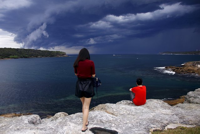 Chinese tourists watch storm clouds moving along the coast towards the city of Sydney, Australia, November 6, 2015. Powerful storms swept across the city on Friday, with the Australian Bureau of Meteorology issuing a warning for severe thunderstorms with large hailstones, heavy rainfall and damaging winds, local media reported. (Photo by David Gray/Reuters)