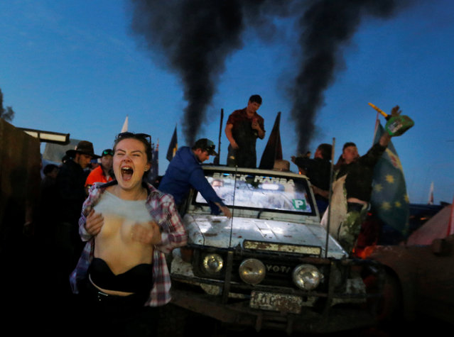 Mel Harris shouts whilst a pick up truck belches smoke on the final night of the Deni Ute Muster in Deniliquin, New South Wales, Australia, October 1, 2016. (Photo by Jason Reed/Reuters)