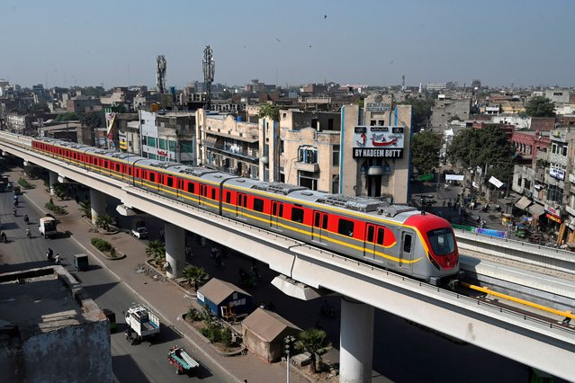 A newly built Orange Line Metro Train (OLMT), a metro project planned under the China-Pakistan Economic Corridor (CPEC), drives through on a track after an official opening in the eastern city of Lahore on October 26, 2020. (Photo by Arif Ali/AFP Photo)