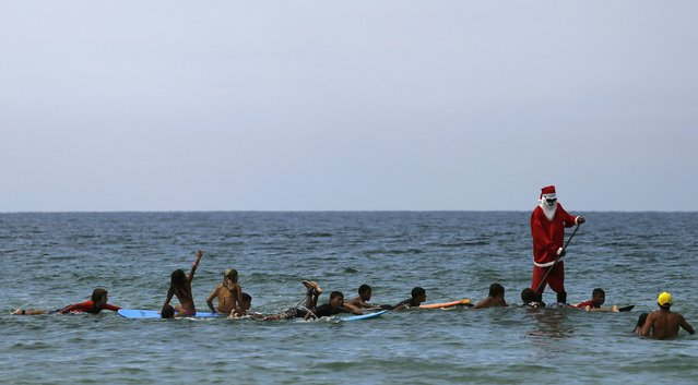 Carlos Bahia, a paddle surfer dressed as Santa Claus, takes to the sea next to children with their boards at the Maresias beach in the state of Sao Paulo December 9, 2014. (Photo by Nacho Doce/Reuters)