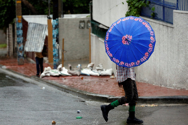 People walk down the street while Hurricane Matthew passes Port-au-Prince, Haiti October 4, 2016. (Photo by Carlos Garcia Rawlins/Reuters)