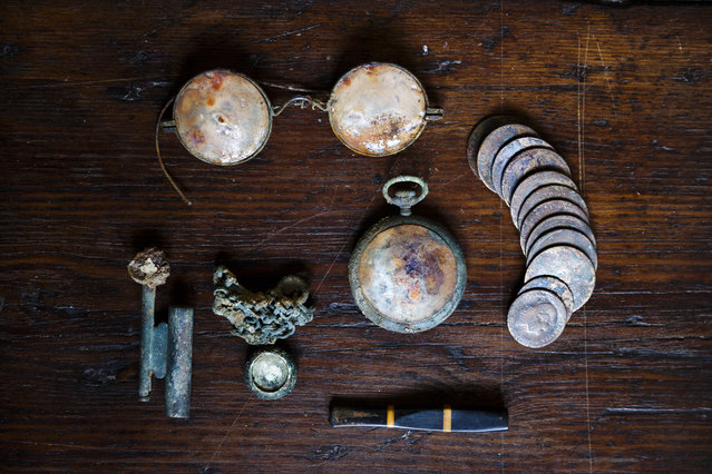 This photo taken on December 17, 2014, shows a lighter, a pendant and its chain, a pocket watch, glasses, coins and a cigarette holder found during the exhumation of a mass grave in Cazalla de la Sierra, Spain. (Photo by Daniel Ochoa de Olza/AP Photo)