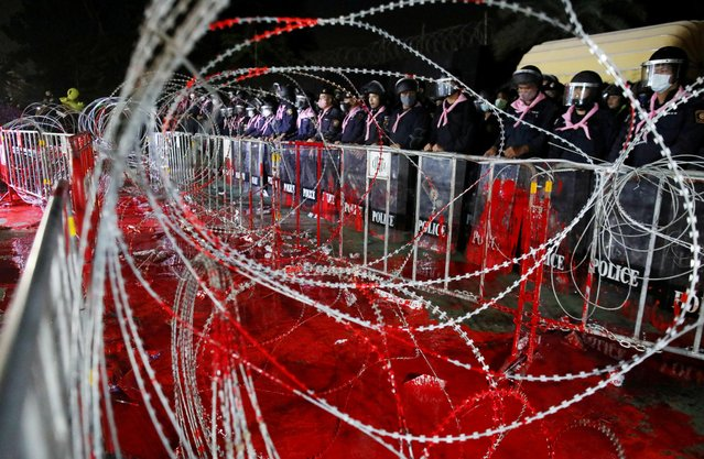 Riot police officers stand guard behind barb wires covered with red paint during a pro-democracy rally demanding Prime Minister Prayuth Chan-ocha to resign and reforms to the monarchy, at 11th Infantry Regiment, in Bangkok, Thailand, November 29, 2020. (Photo by Soe Zeya Tun/Reuters)