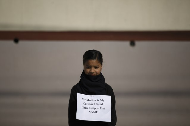 A girl with a placard takes part during a demonstration demanding for the right for Nepali mothers to pass on citizenship to their children, as a new constitution is drafted in Kathmandu December 24, 14. (Photo by Navesh Chitrakar/Reuters)