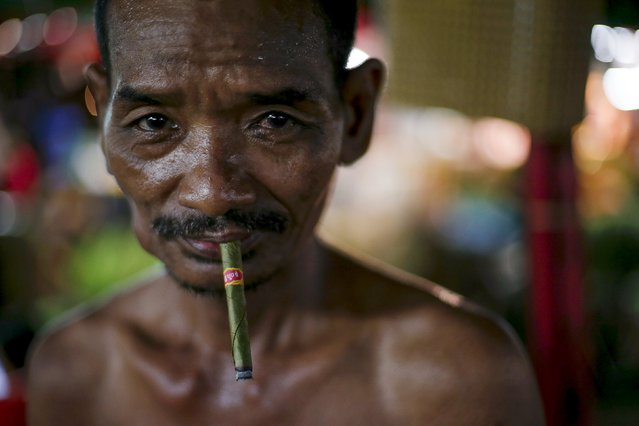 A man smokes while working in a night market in Yangon November 6, 2015. (Photo by Jorge Silva/Reuters)