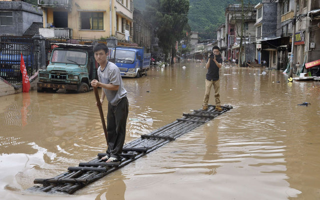 A journalist (R) records a video on a raft as a man paddles along flooded street after heavy downpours hit Jianghua Yao Autonomous County, Hunan province, on May 16, 2013. (Photo by Reuters/Stringer)