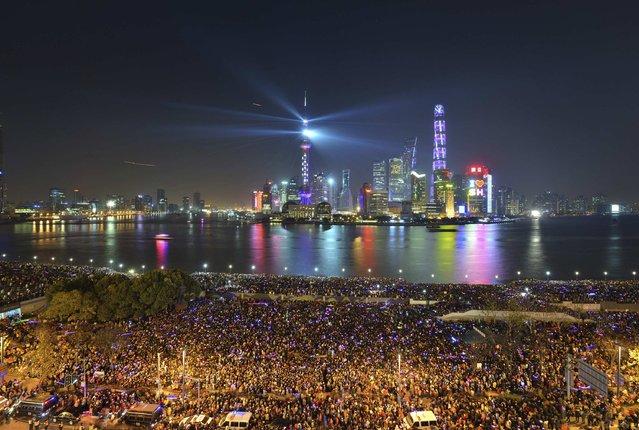 People watch a light show before a stampede incident occurred at the New Year's celebration on the Bund, a waterfront area in central Shanghai December 31, 2014. (Photo by Reuters/Stringer)