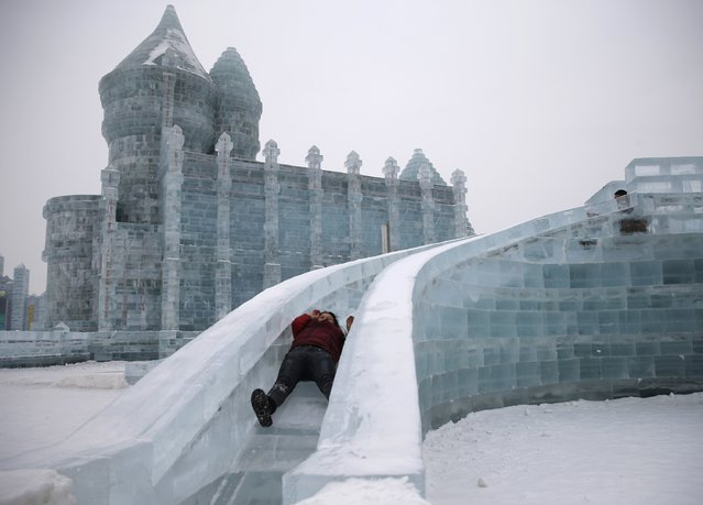 A woman rides a slide on an ice sculpture ahead of the 31st Harbin International Ice and Snow Festival in the northern city of Harbin, Heilongjiang province, January 4, 2015. (Photo by Kim Kyung-Hoon/Reuters)