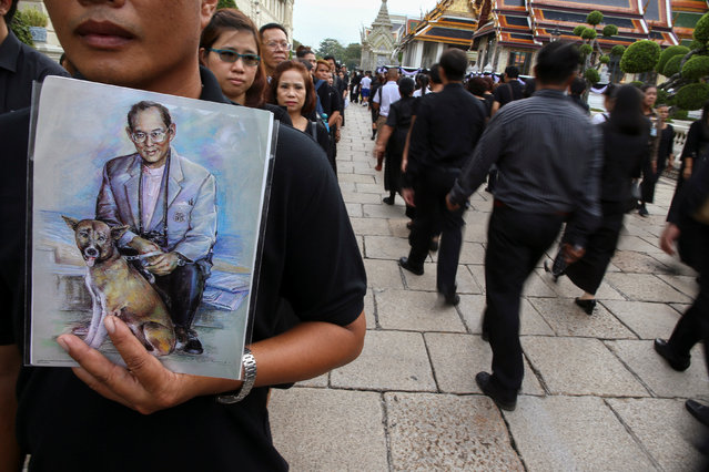 Mourners hold up pictures of Thailand's late King Bhumibol Adulayadej as they walk in line into the Throne Hall at the Grand Palace for the first time to pay respects to his body that is kept in a golden urn in Bangkok, Thailand, October 29, 2016. (Photo by Athit Perawongmetha/Reuters)
