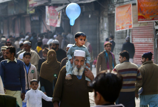 A Pakistani child holds a balloon while he was carried by his grandfather during a rally marking the birthday of Islam's Prophet Muhammad in Rawalpindi, Pakistan, Sunday, January 4, 2015. (Photo by Anjum Naveed/AP Photo)