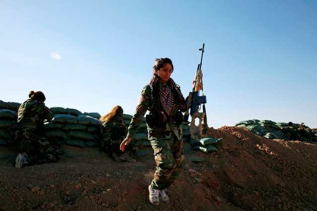 An Iranian-Kurdish female fighter carries her weapon during a battle with Islamic State militants in Bashiqa, near Mosul, Iraq on November 3, 2016. (Photo by Ahmed Jadallah/Reuters)