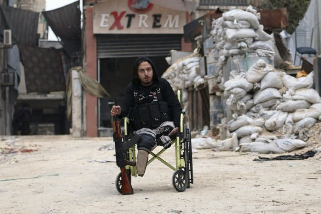 "Abu Nejme, 21, sits on a wheelchair with his weapon as he poses for a picture in Aleppo January 10, 2015. Nejme, a ""Free Syrian Army"" fighter, lost his legs from a barrel bomb about six months ago as he was searching for survivors of a barrel bombing by warplanes loyal to Syria's President Bashar Al-Assad on Al-Sukkari neighbourhood of Aleppo. Nejme says that he still fights with the ""Free Syrian Army"". (Photo by Jalal Al-Mamo/Reuters)"