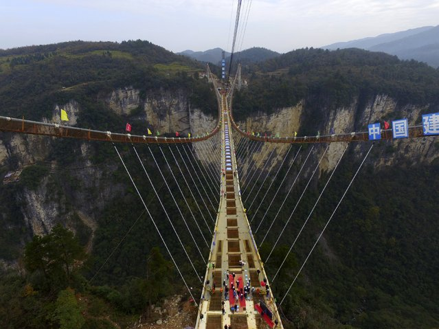 An aerial view shows workers celebrating the completion of the construction of the steel box girder on a glass bridge as it is suspended over a canyon in Zhangjiajie National Park, Hunan province, China, December 3, 2015. The 430-metre-long (1411 feet) glass bridge, which was claimed to be the longest and tallest (300 metres above ground) glass-bottom bridge in the world, is scheduled to finish before May of 2016, local media reported. (Photo by Reuters/Stringer)