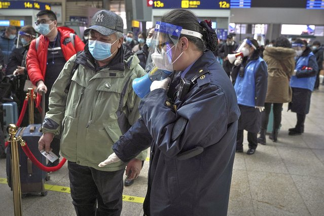 A worker wearing a face mask and face shield to help curb the spread of the coronavirus uses a loud speaker to ask a masked passenger to keep distancing in the line at the South Train Station in Beijing, Thursday, January 28, 2021. Efforts to dissuade Chinese from traveling for Lunar New Year appeared to be working. Beijing's main train station was largely quiet on the first day of the travel rush and estimates of passenger totals were smaller than in past years. (Photo by Andy Wong/AP Photo)