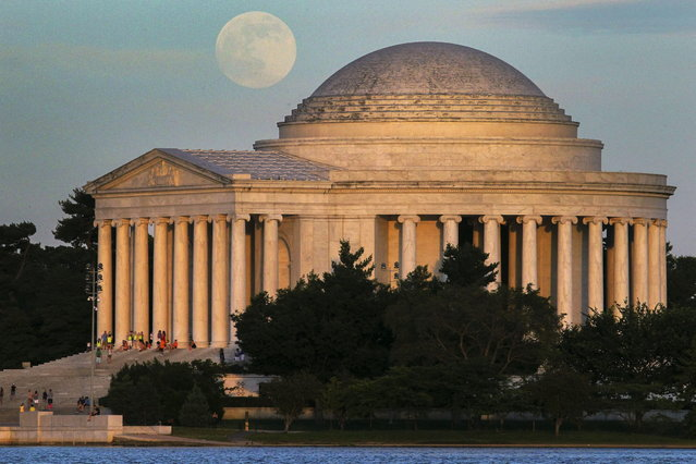 """A full moon rises behind the Jefferson Memorial in Washington Saturday, June 22, 2013. The larger than normal moon called the """"Supermoon"""" happens only once this year as the moon on its elliptical orbit is at its closest point to earth. (Photo by J. David Ake/AP Photo)"""