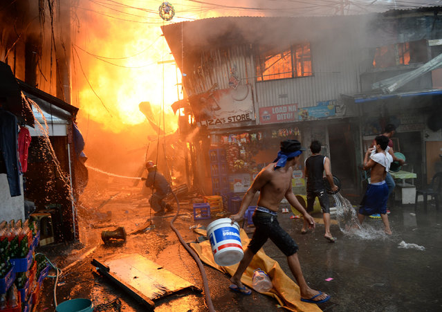 A fireman douses a fire that gutted shanty town near a jail in Manila on December 4, 2015, as residents try to help. Hundreds of inmates were evacuated while thousands were left homeless after a massive fire hit a shanty town in the Philippine capital on December 4, authorities said. (Photo by Ted Aljibe/AFP Photo)