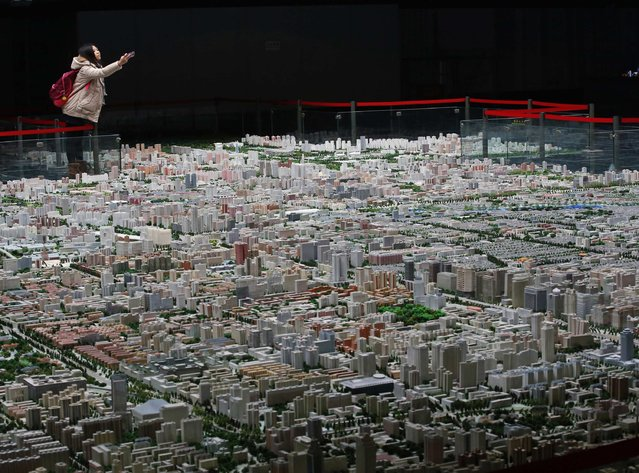 A visitor takes pictures of a model of Beijing's downtowns at the Beijing Planning Exhibition Hall, a museum showcasing the achievement of Beijing urban planning construction, in Beijing in this November 5, 2013 file photo. (Photo by Kim Kyung-Hoon/Reuters)