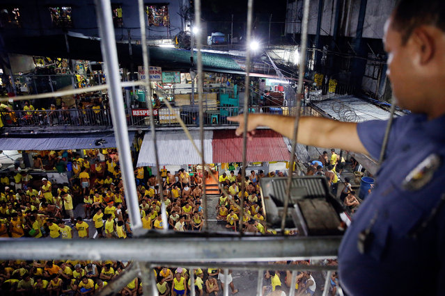 A guard points at inmates gathered at the basketball court for a head count before going to sleep at Quezon City Jail in Manila, Philippines October 18, 2016. (Photo by Damir Sagolj/Reuters)