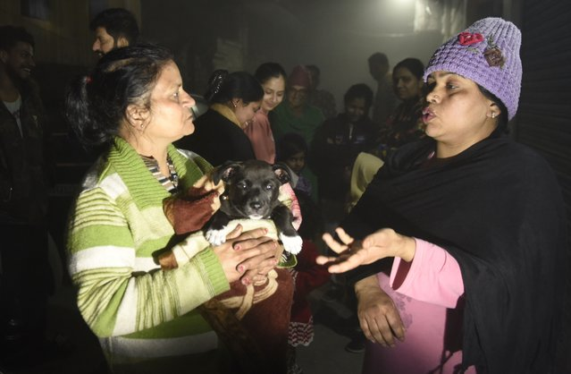 Residents – one holding a puppy – speak on a street in Amritsar late February 12, 2021, after leaving their homes as tremors shook the city in Punjab State north-western India following a powerful earthquake in Tajikistan of a magnitude of 5.9 according to the United States Geological Survey (USGS). (Photo by Narinder Nanu/AFP Photo)