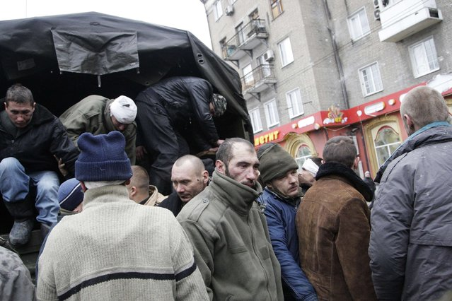 Prisoners of war (POWs), representing Ukrainian armed forces and escorted by members of the armed forces of the separatist self-proclaimed Donetsk People's Republic, get out of a truck as they visit a site near the public transport stop, where civilians were earlier killed on Thursday, in Donetsk, January 22, 2015. (Photo by Alexander Ermochenko/Reuters)
