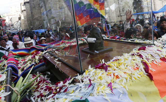 "Crowds accompany the Bolivian deity statuette ""illa of Ekeko"" as it is driven to the Alasitas Fair, in which Ekeko is the central figure, in La Paz, Bolivia, Saturday, January 24, 2015. (Photo by Juan Karita/AP Photo)"