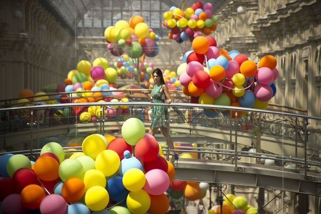 A woman crosses a bridge at GUM, one of the oldest department stores in central Moscow, on July 11, 2013. (Photo by Natalia Kolesnikova/AFP Photo)