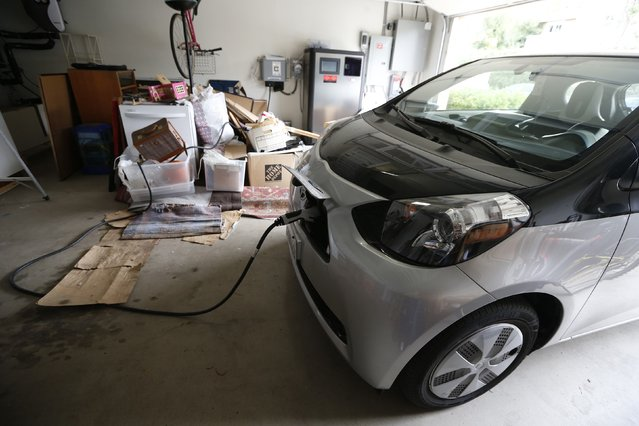 Computer science professor Christa Lopes' Scion IQ electric car is plugged in in her garage next to a residential energy storage unit in Irvine, California January 26, 2015. (Photo by Lucy Nicholson/Reuters)