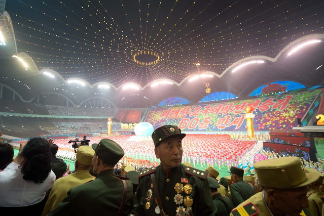 "Noth Korean army veterans watch an ""Arrirang Festival mass games display"" at the 150,000-seat Rungnado May Day Stadiumin Pyongyang on July 26, 2013. Arrirang performances feature some 100,000 participants to create a 'synchronized socialist-realist spectacular in a 90 minute display of gymnastics, dance, acrobatics, and dramatic performance, in a highly politicized package' according to the China-based North Korean travel company Koryo Tours. North Korea is preparing to mark the 60th anniversary of the end of the Korean War which ran from 1950 to 1953, with a series of performances, festivals, and cultural events culminating with a large military parade. (Photo by Ed Jones/AFP Photo)"