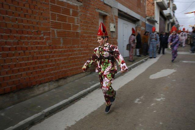 "A boy jumps at the San Blas (Saint Blaise) procession during the ""Endiablada"" festival in Almonacid del Marquesado, in central Spain February 3, 2015. (Photo by Susana Vera/Reuters)"