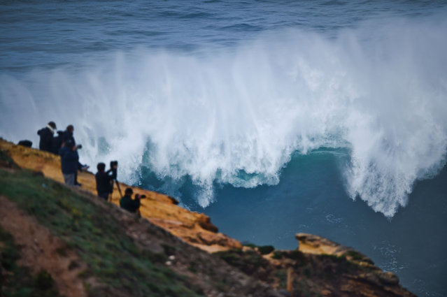 People take pictures from the cliff during a big- wave surfing session at Praia do Norte in Nazare on November 19, 2016. (Photo by Patricia de Melo Moreira/AFP Photo)