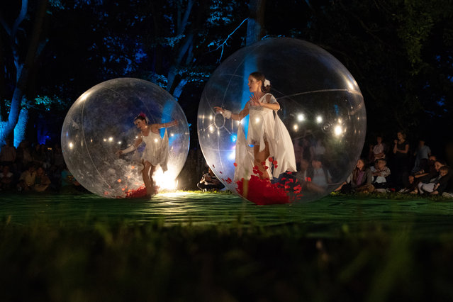 Dancers perform inside of transparent balls during the Botanical Night at Botanical Garden in Berlin, Germany, 20 July 2018. During the Botanical Night a 16 kilometre long path along the flower beds and several themed gardens are illuminated and guide to many attractions. (Photo by Hayoung Jeon/EPA/EFE)