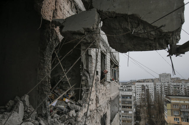 A municipal official looks through the window of a residential block, which was damaged by a shelling on Wednesday according to locals, in Donetsk, February 5, 2015. (Photo by Maxim Shemetov/Reuters)