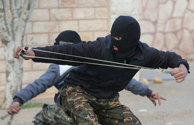 A Palestinian protester uses a sling to hurl stones at Israeli troops during clashes in the West Bank village of Silwad, near Ramallah December 26, 2015. (Photo by Mohamad Torokman/Reuters)
