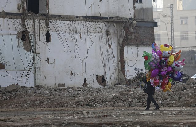 A balloon vendor walks in front of a partially demolished building at a demolition site in Kunming, Yunnan province February 4, 2015. China's services sector grew at the slowest pace in six months in January as growth in new business weakened, a private survey showed, raising expectations that policymakers may unveil more stimulus steps to avert a sharper slowdown in the world's second-largest economy. (Photo by Reuters/Stringer)