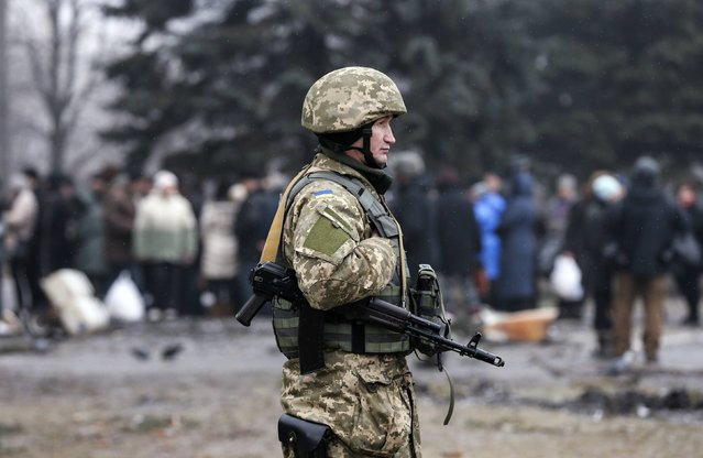 A Ukrainian serviceman patrols the area as people stand in line to receive humanitarian aid near a delivery point in the government forces-controlled town of Debaltseve, Donetsk region February 6, 2015. (Photo by Maxim Shemetov/Reuters)