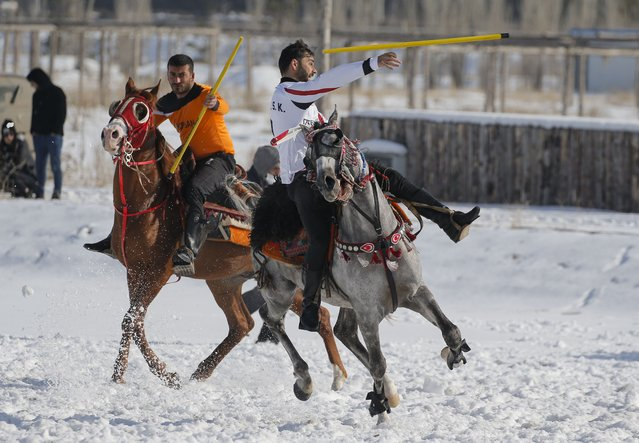 A rider throws the javelin during a game of Cirit, a traditional Turkish equestrian sport that dates back to the martial horsemen who spearheaded the historical conquests of central Asia's Turkic tribes, between the Comrades and the Experts local sporting clubs, in Erzurum, eastern Turkey, Friday, March 5, 2021. (Photo by Kenan Asyali/AP Photo)