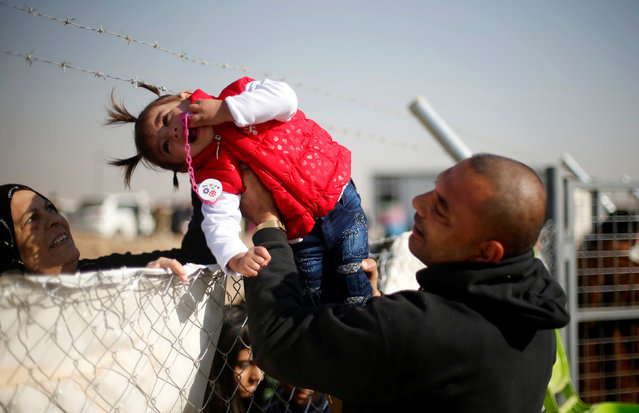 A displaced Iraqi man, who fled the Islamic State stronghold of Mosul, holds his daughter to be seen by her grandmother through a fence at Khazer camp, Iraq November 28, 2016. (Photo by Mohammed Salem/Reuters)