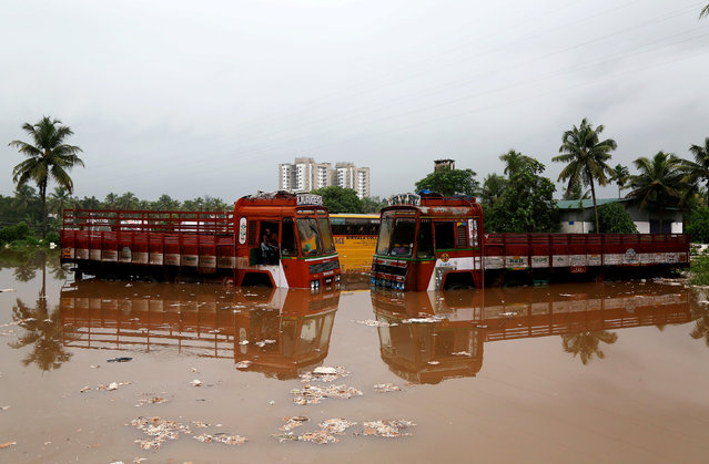 Partially submerged trucks are seen surrounded by floodwaters at a parking bay after the opening of Idamalayr, Cheruthoni and Mullaperiyar dam shutters following heavy rains, on the outskirts of Kochi, August 16, 2018. (Photo by Sivaram V/Reuters)