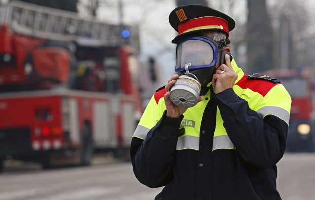 """A Catalan """"Mosso d'Esquadra"""" police officer wearing a gas mask speaks on a mobile phone after an explosion at a chemical plant caused a toxic cloud to spread over Igualada near Barcelona February 12, 2015. (Photo by Reuters/Stringer)"""